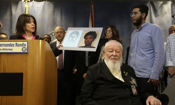 State Attorney Katherine Fernandez Rundle, left, holds up a photograph of Deandre Charles during a news conference where officials announced the arrest of Charles in connection with the death of Rabbi Joseph Raksin, Wednesday, Dec. 9, 2015, in Miami. Raksin was killed during an attempted robbery while visiting Miami from New York in August 2014. Looking on are Raksin's children Shuli Labkowski Raksin, second from right, and Mendel Raksin, right, standing. Seated is Rabbi Pinchas Weberman, a chaplain for the Miami-Dade police department. (AP Photo/Lynne Sladky)