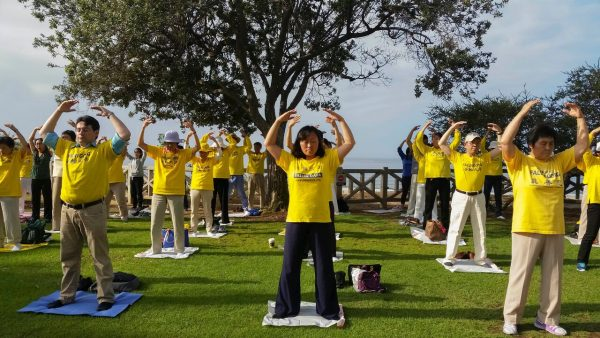 Peaceful standing meditation is one of four standing exercises of the Falun Gong practice. Falun Gong practitioners do the exercises at Santa Monica beach on Oct. 15, 2015. (Cat Rooney/Epoch Times)