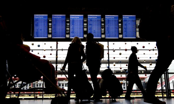 In this Nov. 29, 2015 file photo, travelers walk to their gates at O'Hare International Airport in Chicago.  Airlines are shifting the timing of thousands of flights, even adding dozens of redeyes, as they try to avoid delays while hauling millions of passengers from now through the Christmas weekend. Success or failure could all depend on the weather.(AP Photo/Nam Y. Huh, File)