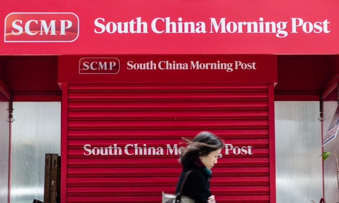 A pedestrian walks past a closed newsstand designed with the logo of the 'South China Morning Post' (SCMP) in Hong Kong on Dec. 12, 2015, following its acquisition by Chinese Internet giant Alibaba of the English-language newspaper. (Anthony Wallace/AFP/Getty Images)
