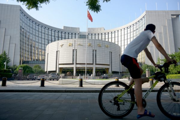 A man rides his bike in front of the People's Bank of China in Beijing on Aug. 12, 2015. (Wang Zhao/AFP/Getty Images)