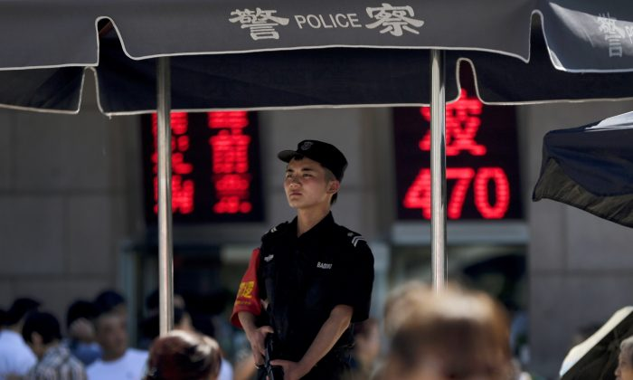 An armed policeman at a police booth at a crowded railway station in Beijing, China, on Sept. 3, 2014. Beijing's tight controls and monopoly on the narrative make it difficult to independently assess if the lethal action has been justified. And Chinese authorities prevent most reporting by foreign journalists inside Xinjiang, making it nearly impossible to confirm the state media numbers. (AP Photo/Andy Wong)