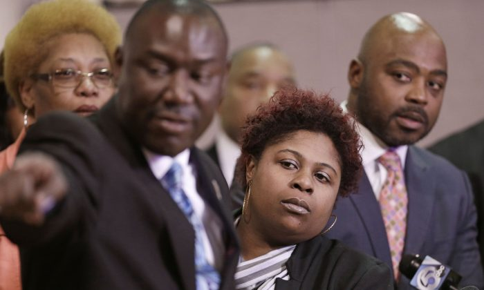 Samaria Rice (C), the mother of Tamir Rice, a 12-year-old boy fatally shot by a Cleveland police officer, watches the video of Tamir's shooting during a news-conference in Cleveland on March 3, 2015. Attorney Benjamin Crump (L), and attorneys Walter Madison (R) watch. Attorneys for the family of Tamir Rice have asked a prosecutor to allow their use-of-force experts to testify before the grand jury. (AP Photo/Tony Dejak)