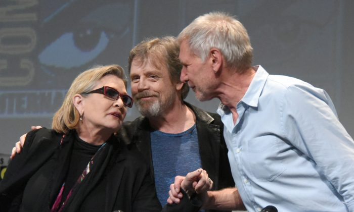 "Carrie Fisher, from left, Mark Hamill, and Harrison Ford attend Lucasfilm's ""Star Wars: The Force Awakens"" panel on day 2 of Comic-Con International on Friday, July 10, 2015, in San Diego, Calif. (Photo by Richard Shotwell/Invision/AP)"