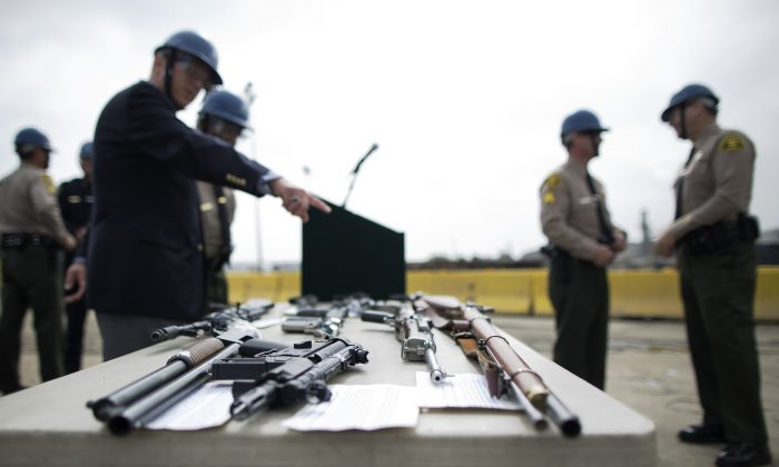Officials look at confiscated guns prior to the destruction of approximately 3,400 guns and other weapons at the Los Angeles County Sheriffs' 22nd annual gun melt at Gerdau Steel Mill on July 6, 2015 in Rancho Cucamonga, California. (David McNew/Getty Images)