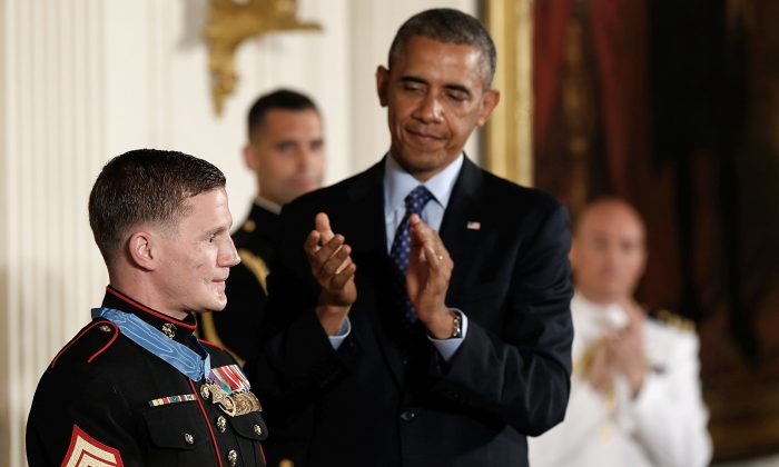 Retired Marine Cpl. William 'Kyle' Carpenter is applauded by U.S. President Barack Obama after receiving the Medal of Honor during a ceremony in the East Room of the White House on June 19, 2014 in Washington, DC. Carpenter received the medal for taking the blast from a grenade to protect fellow Marines and sustained major wounds. Carpenter is the eighth living recipient chosen for the high honor.  (Photo by Win McNamee/Getty Images)