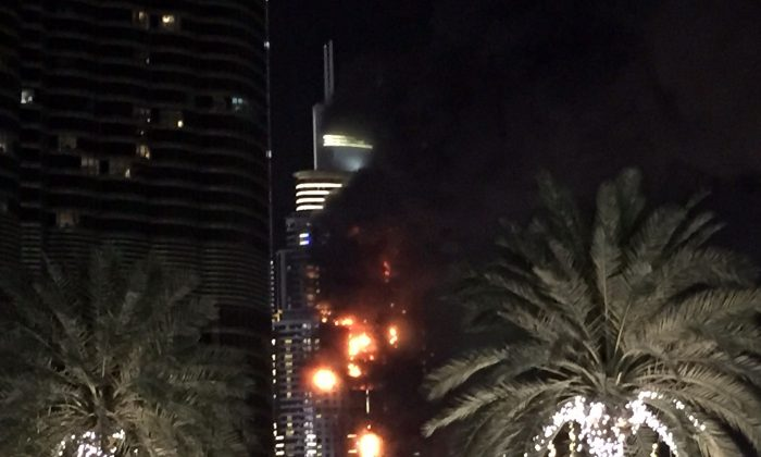 A fire runs up some 20 stories of a building in Dubai, United Arab Emirates, Thursday, Dec. 31, 2015. The fire broke out Thursday in a residential building near Dubai's massive New Year's Eve fireworks display. It was not immediately clear what caused the fire near the Burj Khalifa, the world's tallest skyscraper at 828 meters (905 yards). (AP Photo/Jon Gambrell)