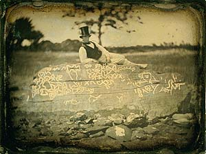 An 1853 reversed image of Seth Eastman (known for documenting Native American life in the 1800s) on top of the boulder known as Dighton Rock. (Public Domain)