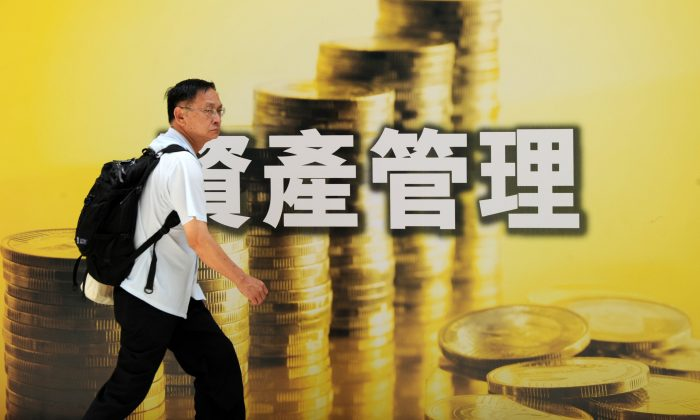 A pedestrian walks past an advertisement for investment related products in Hong Kong on June 21, 2010.  (Mike Clarke/AFP/Getty Images)