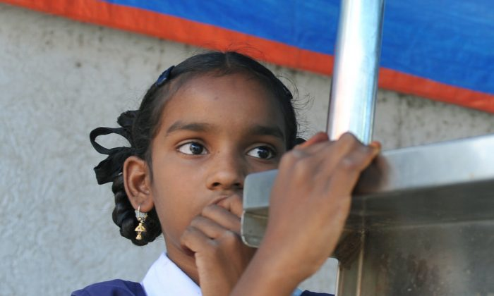 An Indian schoolgirl stands at her father's temporary tea stall in Hyderabad on Oct. 11, 2012, on the occasion of the first 'International Day of the Girl Child.' (Noah Seelam/AFP/GettyImages)