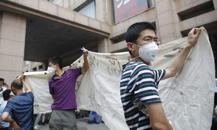 Residents, whose homes were destroyed in the explosion at a chemical warehouse last week, protest outside the hotel where authorities are holding a press conference in Tianjin on August 17, 2015.(STR/AFP/Getty Images)