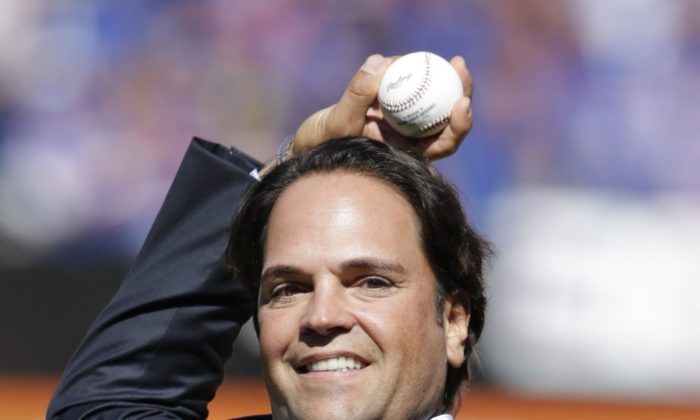 Former New York Mets catcher Mike Piazza throws out the ceremonial first pitch before a baseball game against the Milwaukee Brewers, following a ceremony inducting him into the Mets Hall of Fame, in New York. (AP Photo/Kathy Willens, File)