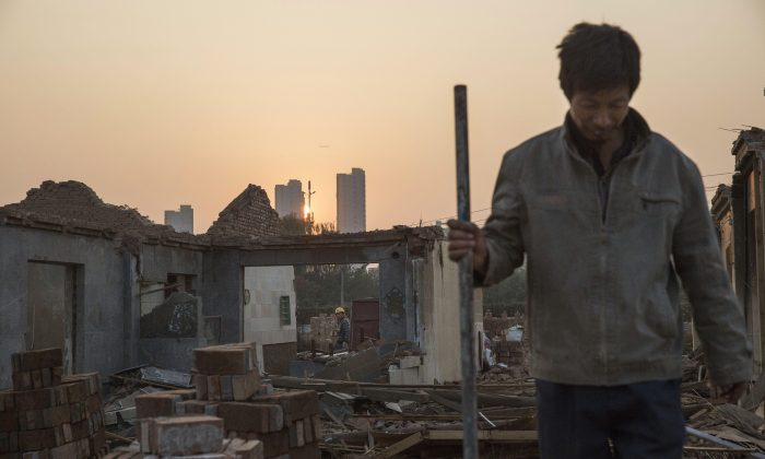 Chinese laborers demolish a home in Gucheng Village, in the Tongzhou District of Beijing, on Oct. 16, 2015. Beijing municipal offices will be moved from the center of the city to outlying areas as part of an ambitious government project to create an urban megacity in northern China. (Kevin Frayer/Getty Images)