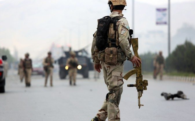 Afghan security forces gather at the site of a suicide attack after clashes with Taliban fighters in front of the Parliament, in Kabul, Afghanistan, on Monday, June 22. (AP Photo/Rahmat Gul)
