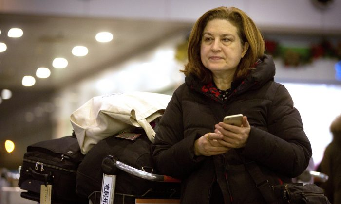 French journalist Ursula Gauthier, a reporter in China for the French news magazine L'Obs, checks her cellphone as she waits at Bejing Capital International Airport in Beijing on Dec. 31, 2015. (AP Photo/Mark Schiefelbein)