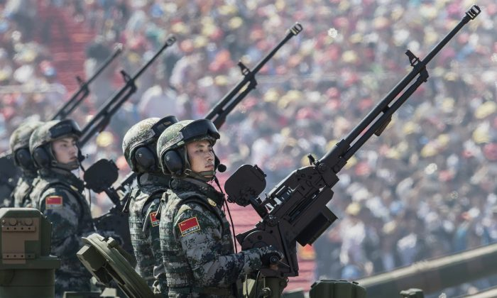 Chinese soldiers ride in an armoured vehicle as they hold machine guns while passing in front of Tiananmen Square and the Forbidden City during a military parade on September 3, 2015 in Beijing, China. (Kevin Frayer/Getty Images)
