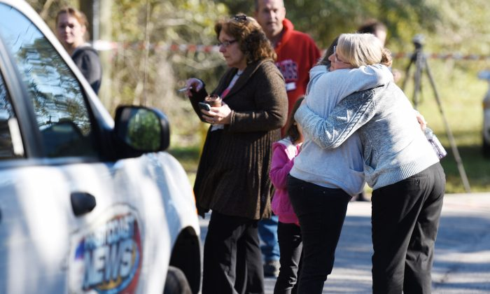 Maggie Smith, one of the people involved in the search for missing toddler Lonzie Barton hugs Judy Bearfoot before a news conference Monday, Jan. 11, 2016, in Jacksonville, Fla. Authorities found human remains Monday that they believe are those of a Florida toddler who was reported missing last summer. The remains are believed to be those of Lonzie Barton, Jacksonville Sheriff's Office Chief of Investigations Tom Hackney said. (Bob Self/The Florida Times-Union via AP)