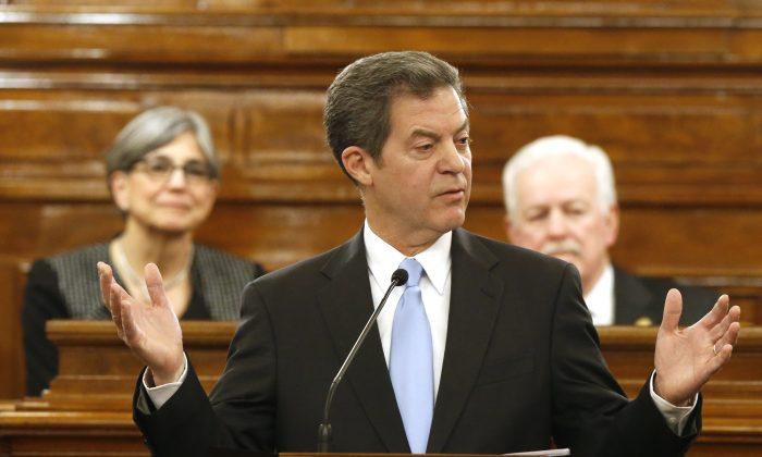 Kansas Gov. Sam Brownback addresses a joint session of the Kansas House and Senate during the annual State of the State speech in Topeka, Kan., Tuesday, Jan. 12, 2016. (Bo Rader/The Wichita Eagle via AP)