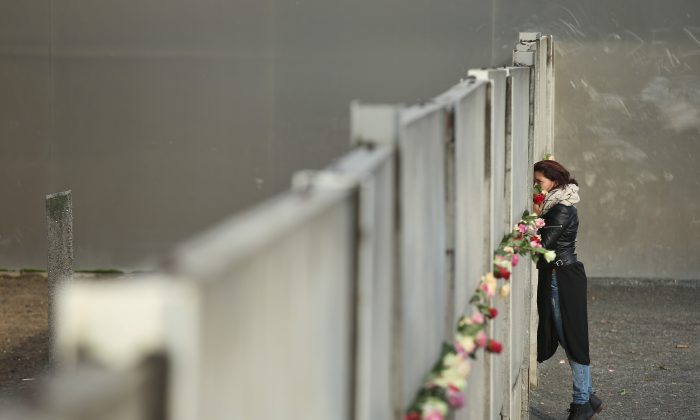 A woman places flowers at the remains of the Berlin Wall on November 9, 2015, the 26th anniversary of its demolition. From 1961 to 1989, the Wall, built to keep East Germans from emigrating to the democratic west, was a symbol of the Cold War and Soviet communism. (Sean Gallup/Getty Images)
