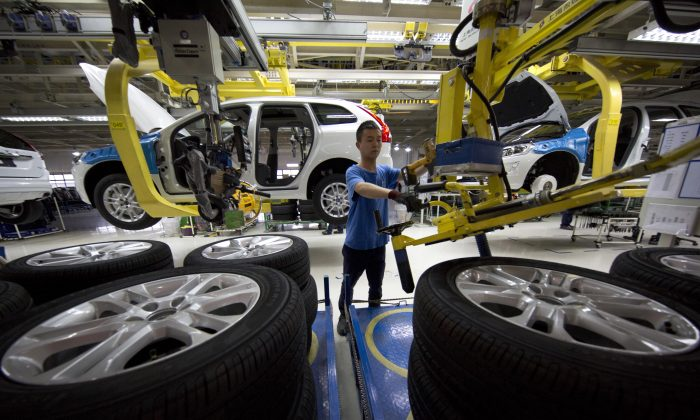 A worker installs wheels on a car at a Volvo factory in Chengdu in southwestern China's Sichuan province, on April 21, 2015. (AP Photo/Ng Han Guan)