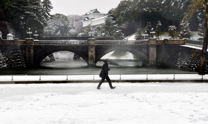 A man walks on a snow covered field in front of the Imperial Palace in Tokyo on January 18, 2016. (YOSHIKAZU TSUNO/AFP/Getty Images)