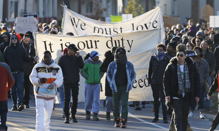 Black Lives Matter protesters and supporters march from the Minneapolis Police Department's Fourth Precinct to the Federal Building in Minneapolis, Tuesday, Nov. 24, 2015. The fatal shooting of Jamar Clark, a black man, by a Minneapolis police officer, has pushed racial tensions in the city's small but concentrated minority community to the fore, with the police precinct besieged by the makeshift encampment and many protesters. (AP Photo/Jim Mone)