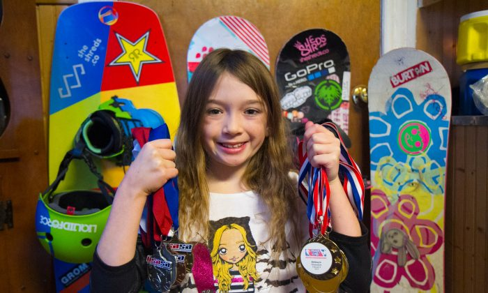 Ashlyn Overland, 9, stands in front of her boards holding her snowboarding medals at her home in Port Jervis on Jan. 19, 2016. (Holly Kellum/Epoch Times)