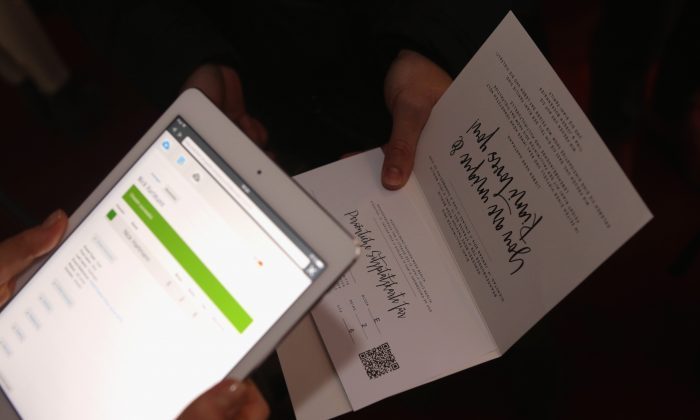 A visitor holds an invite during the Mercedes-Benz Fashion Week Berlin Autumn/Winter 2016 at Brandenburg Gate on January 19, 2016 in Berlin, Germany. (Adam Berry/Getty Images for IMG)