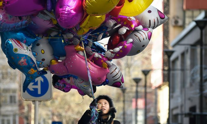 A balloon vendor waits for customers outside a shop in Beijing on Dec. 24, 2014. (Wang Zhao/AFP/Getty Images)