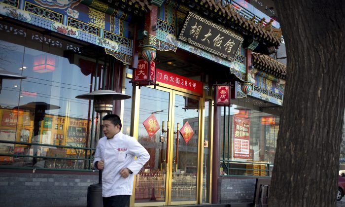 A man in a chef's uniform jogs past a branch of the Hu Da hot pot restaurant chain in Beijing on Jan. 22, 2016. (AP Photo/Mark Schiefelbein)