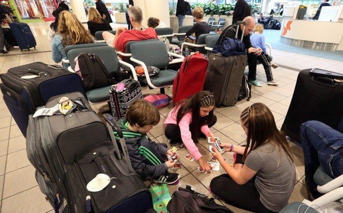Liam Everett (L), 8, Chloe Betts (C), 10, and Isabella Everett, 10, of North Carolina, play a card game, at Orlando International Airport in Orlanda, Fla., on Jan. 22, 2016. (Red Huber/Orlando Sentinel via AP)