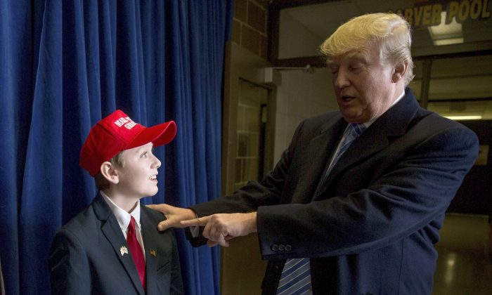 Republican presidential candidate Donald Trump speaks a young supporter as he arrives for a rally at Muscatine High School in Muscatine, Iowa, Sunday, Jan. 24, 2016. (AP Photo/Andrew Harnik)