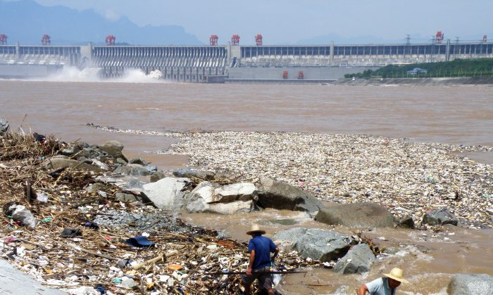 Two workers clean up trash along the bank of the Yangtze River near the Three Gorges Dam in Yichang, in central China's Hubei Province on Aug. 1, 2010. (STR/AFP/Getty Images)