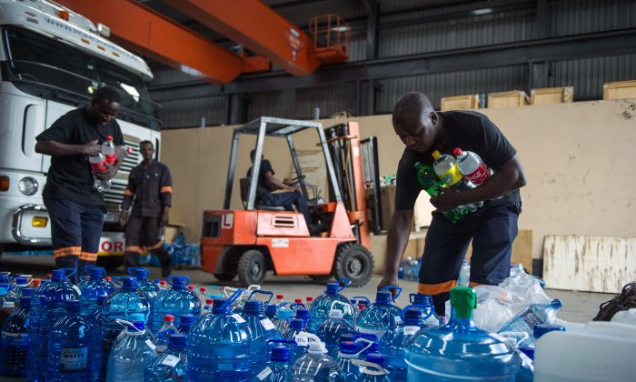 Factory workers pile up donated water bottles by South African residents from the Johannesburg outskirts town of Benoni to be delivered in drought stricken rural communities, on January 15, 2016 in Benoni, South Africa (MUJAHID SAFODIEN/AFP/Getty Images).