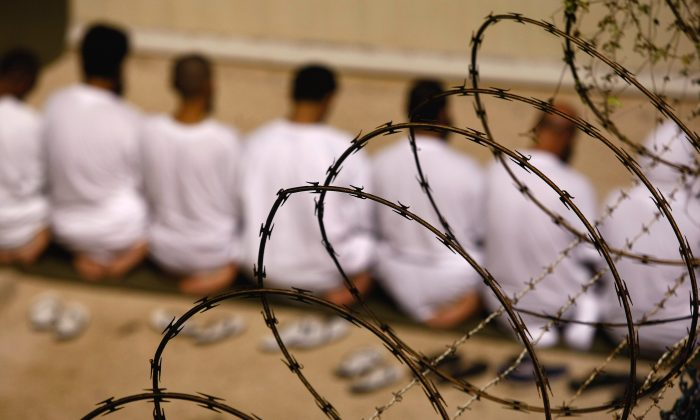 A group of detainees kneels during an early morning Islamic prayer at the Guantánamo Bay Naval Base in Cuba on Oct. 28, 2009. (John Moore/Getty Images)