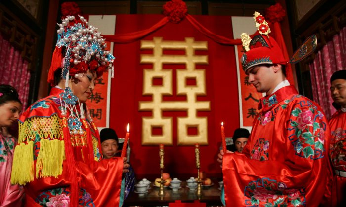 A newlywed couple, the groom from France and bride from China, attend their Chinese style wedding ceremony at the Grand Sight Garden on May 5, 2007 in Beijing, China. (China Photos/Getty Images)