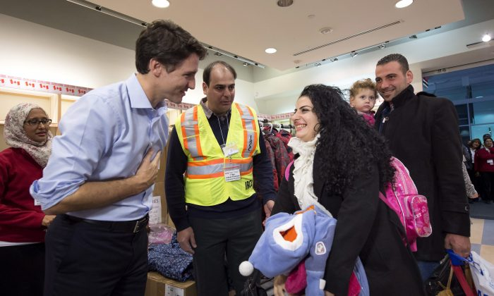 Canadian Prime Minister Justin Trudeau (L) greets refugees fleeing from Syria as they arrive at the Pearson International Airport in Toronto, on Dec. 11. (Nathan Denette/The Canadian Press via AP)