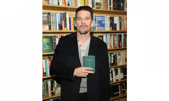 """Actor/author Ethan Hawke poses with a copy of """"Rules For A Knight"""" at a book signing in New York City on Nov. 10, 2015. (Jemal Countess/Getty Images)"""