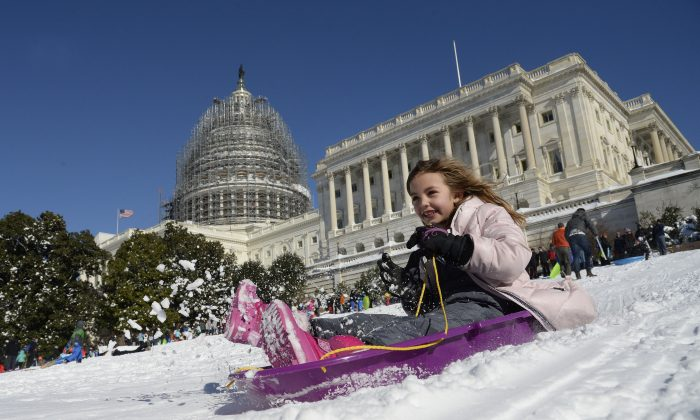 "A young girl is sliding on the West Lawn of the US Capitol on Jan 24, 2016. The storm – dubbed ""Snowzilla"" – killed at least 47 people after it walloped several states over 36 hours on Friday and Saturday, affecting an estimated 85 million residents who were told to stay off the roads and hunker down in doors for their own safety. (OLIVIER DOULIERY/AFP/Getty Images)"