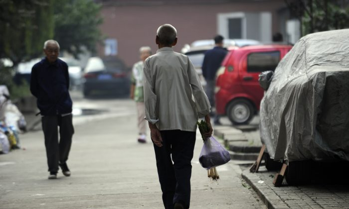 This picture taken on Sept. 7, 2012 shows an elderly man making his way home after buying some vegetables from a market in Beijing. Seniors will be the first to have their pensions cut as China edges closer to a financial cliff, says He Qinglian. (Wang Zhao/AFP/Getty Images)