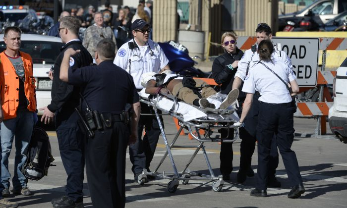 Paramedics transport a man to an awaiting ambulance at the National Western Complex in Denver on Jan. 30, 2016. Denver police say multiple people were injured in a deadly stabbing and shooting at The Colorado Motorcycle Expo. (Andy Cross/The Denver Post via AP)