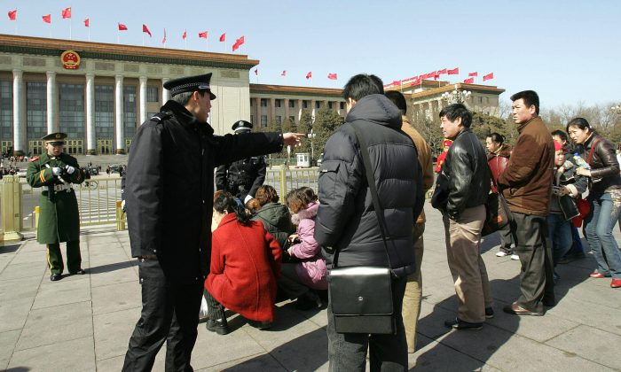 A policeman (L) shouts at suspected protesters to make them kneel down in Beijing on March 7, 2005. Chinese officials have interesting takes on some social issues. (Peter Parks/AFP/Getty Images)