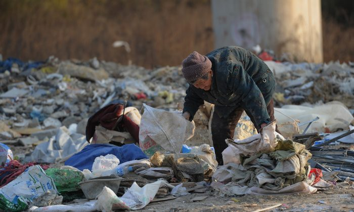 An elderly scavenger picks up construction waste from a garbage dump in Hefei, Anhui Province on Dec. 9, 2012. Police roughed up two senior scavengers for violating traffic in Henan Province. (STR/AFP/Getty Images)