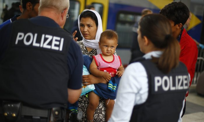 German federal police officers talk to a Afghan family after they arrived the main station in Rosenheim, southern Germany, Tuesday, July 28, 2015.  (AP Photo/Matthias Schrader)