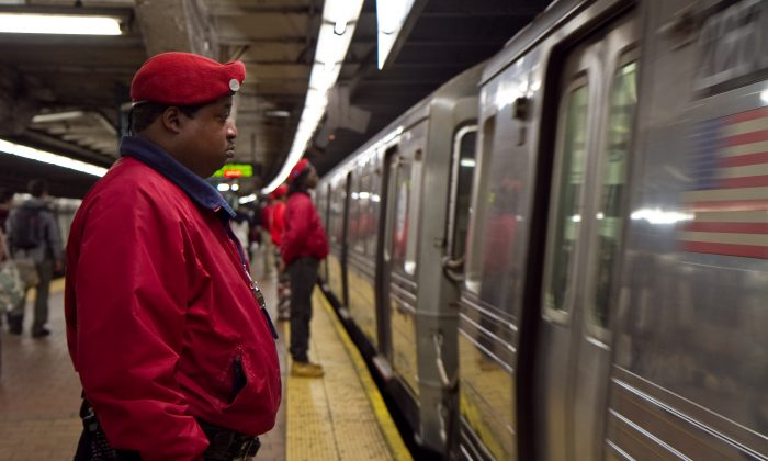 Members of the Guardian Angels wait to board the B train at the 34th Street station in Manhattan and ride it up all the way through to the Bronx on Jan. 3, 2013. (Benjamin Chasteen/Epoch Times)