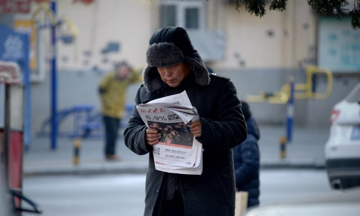 "A man reads a newspaper with a front page headline that reads  ""China's GDP grows at 6.9 percent""  in Beijing on Jan. 19, 2016. China's economy grew at its slowest pace in a quarter of a century last year as it undergoes a difficult transition. (WANG ZHAO/AFP/Getty Images)"