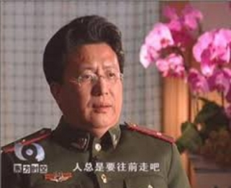 "Dr. Shen Zhongyang is interviewed on Chinese television in his paramilitary uniform. The subtitle says ""humankind will always make progress."""
