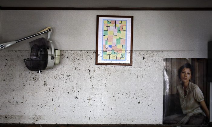 The waterline from the March 11 tsunami is left on the wall at the barber shop in Ishinomaki, Miyagi Prefecture, northeastern Japan, Saturday, April 16, 2011. The water in many places along Japan's northeastern Pacific coast struck by tsunami rose above head level, and everything below the waterline was destroyed or left covered by mud. (AP Photo/Sergey Ponomarev)