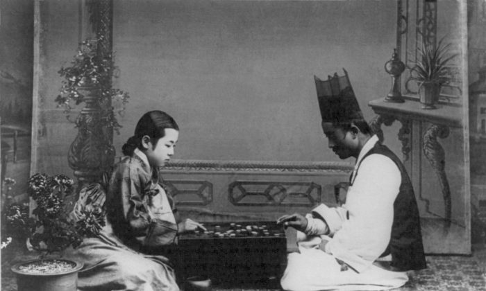 A Korean man and woman play a game of Go in the early 1900s (Public Domain)