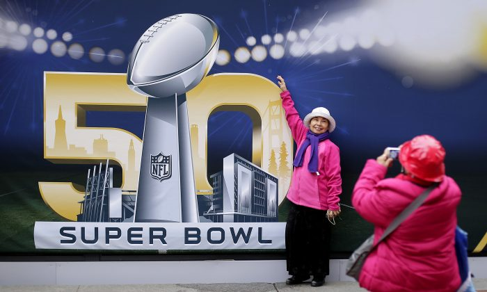 Angie Bagares poses for a photo in front of a Super Bowl 50 sign at Super Bowl City Wednesday, Feb. 3, 2016, in San Francisco. (AP Photo/Charlie Riedel)